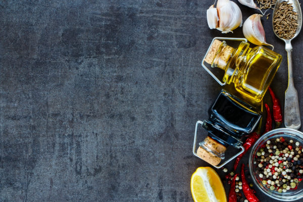Close up of cooking ingredients (lemon fresh garlic olive oil balsamic vinegar and spices) on dark vintage background with space for text top view banner. Healthy food vegan or diet nutrition concept.
