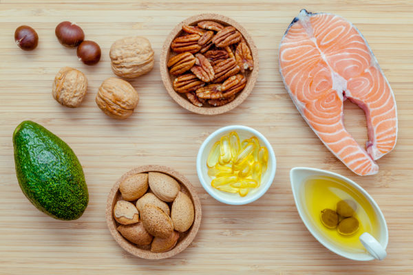 Selection food sources of omega 3 and unsaturated fats. Super food high omega 3 and unsaturated fats for healthy food. Almond pecan hazelnutswalnuts olive oil fish oil salmon and avocado on wooden background .