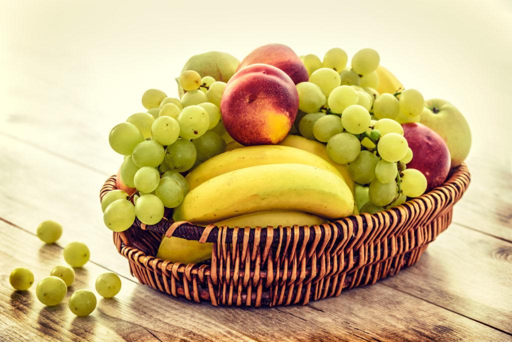 Un panier de fruits est sur la table. Remplacer les sucreries par des fruits est un bon point de départ pour une meilleure santé.